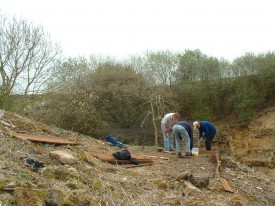 Building a viewing platform on a slope opposite the rock face.